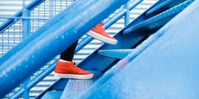 red shoes walking up blue metal stairs