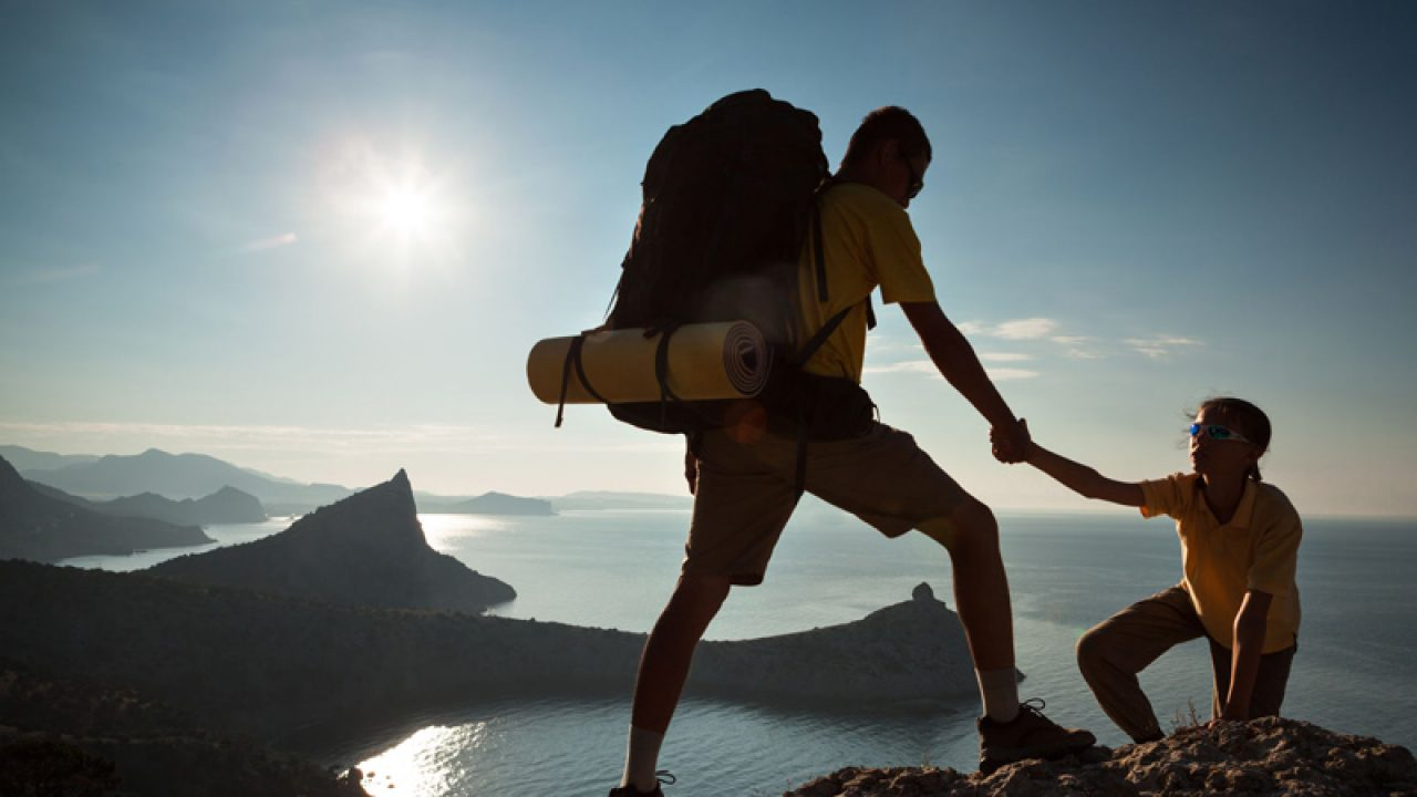 guy pulling up girl in a yellow shirt rock climbing