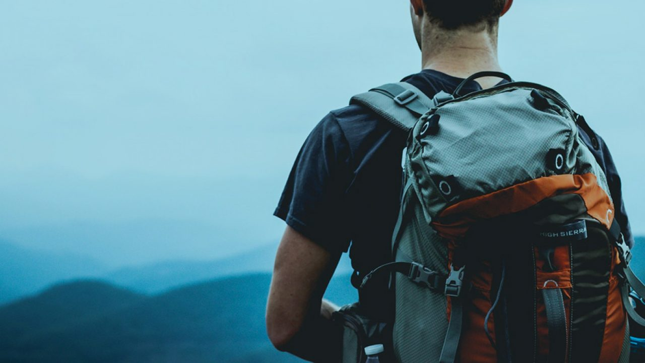 guy with backpack looking out into distance